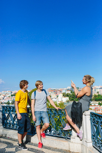 Portugal, Lisbon, Woman taking photo of two men in cityの写真素材 [FYI02199938]