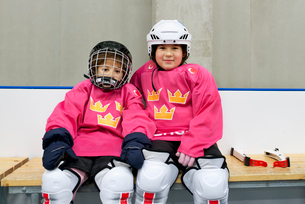 Sweden, Girls (4-5, 6-7) in ice hockey uniform sitting on benchの写真素材 [FYI02199963]
