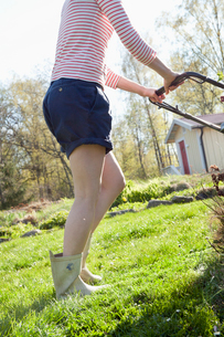 Sweden, Ostergotland, Vikbolandet, Low-section of woman mowing lawnの写真素材 [FYI02200084]