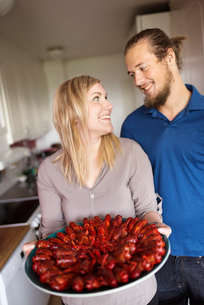 Sweden, Man and woman holding crayfish on plateの写真素材 [FYI02200125]
