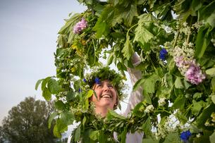 Sweden, Skane, Woman arranging floral wreath for midsummer celebrationsの写真素材 [FYI02200143]