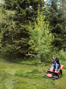 Finland, Uusimaa, Espoo, Man on lawn mower in parkの写真素材 [FYI02200151]