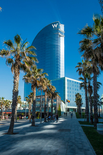 Spain, Catalonia, Barcelona, Alley leading towards high rise hotelの写真素材 [FYI02200164]