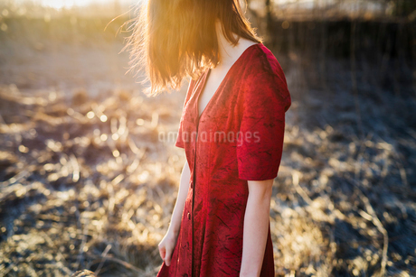 Finland, Varsinais-Suomi, Young red hair woman in red dress standing in sunlightの写真素材 [FYI02200167]