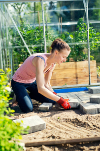 Finland, Paijat-Hame, Mid adult woman paving in front of greenhouseの写真素材 [FYI02200214]