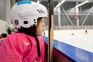 Sweden, Girl (6-7) in ice hockey uniform by railingの写真素材 [FYI02200247]