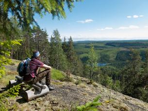 Sweden, Medelpad, Storberget naturreservat, Hiker sitting on wooden bench in forest and looking at vの写真素材 [FYI02200257]