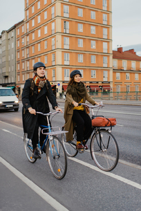 Sweden, Uppland, Stockholm, Vasatan, Sankt Eriksgatan, Man and woman cycling on city streetの写真素材 [FYI02200282]