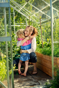 Finland, Heinola, Paijat-Hame, Woman embracing girl (4-5) in glasshouseの写真素材 [FYI02200285]