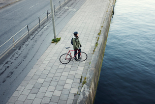 Sweden, Sodermanland, Stockholm, Sodermalm, Slussen, Mid adult man with bicycle standing on river baの写真素材 [FYI02200296]