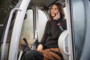 Sweden, Uppland, Nacka, Woman talking on phone in bulldozerの写真素材 [FYI02200304]