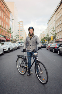 Sweden, Sodermanland, Stockholm, Sodermalm, Hornstull, Mid adult man standing by his bicycle on streの写真素材 [FYI02200319]