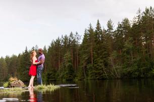 Sweden, Vastmanland, Bergslagen, Svartalven, Mid adult couple embracing in riverの写真素材 [FYI02200327]