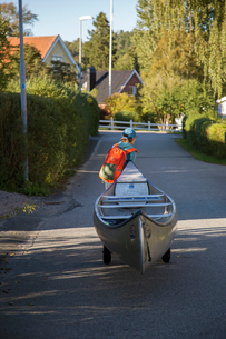 Sweden, Vastergotland, Lerum, Savean, Boy (12-13) pulling canoe up roadの写真素材 [FYI02200347]