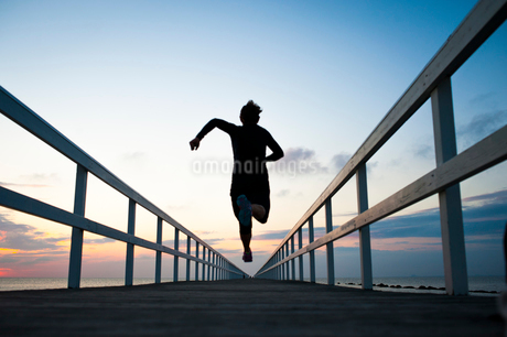 Sweden, Skane, Malmo, Young woman running on pier at sunsetの写真素材 [FYI02200355]
