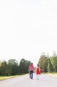 Sweden, Vastmanland, Bergslagen, Hallefors, Rear view of mid adult couple walking on rural roadの写真素材 [FYI02200377]