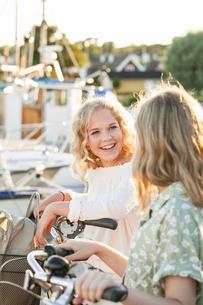 Sweden, Blekinge, Hallevik, Two teenage girls(14-15, 16-17) with bicycles at marina bayの写真素材 [FYI02200391]