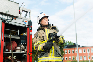 Sweden, Sodermanland, Sodertalje, Female firefighter using fire hose next to truckの写真素材 [FYI02200397]