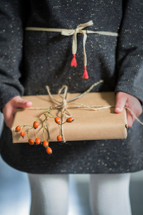 Sweden, Girl (6-7) holding wrapped Christmas presentの写真素材 [FYI02200402]