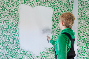 Sweden, Vastra Gotaland, Gullspang, Runnas, Woman painting white over green floral wallpaperの写真素材 [FYI02200408]