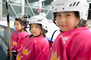 Sweden, Girls (4-5, 6-7) in ice hockey uniform standing by railingの写真素材 [FYI02200429]