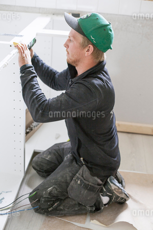 Sweden, Carpenter installing furnitureの写真素材 [FYI02200441]