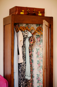 Italy, Liguria, Imperia, Diano Marina, Clothes hanging in open wooden wardrobeの写真素材 [FYI02200542]