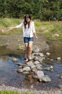 Finland, Uusimaa, Helsinki, Lauttasaari, Young woman crossing river on stonesの写真素材 [FYI02200548]