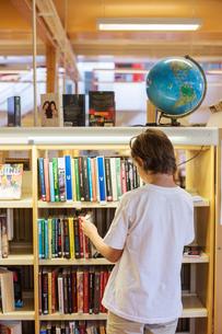 Sweden, Boy (12-13) choosing book in libraryの写真素材 [FYI02200560]