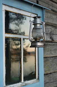 Finland, Pirkanmaa, Ruovesi, Silver lantern hanging in front of wooden cottageの写真素材 [FYI02200565]