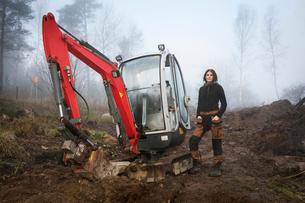 Sweden, Uppland, Nacka, Woman standing by bulldozer in forestの写真素材 [FYI02200576]