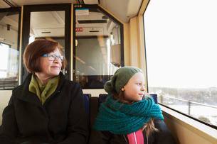 Sweden, Stockholm, Girl (10-11) sitting with grandmother in tram and looking through windowの写真素材 [FYI02200584]