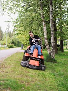 Finland, Uusimaa, Espoo, Man on lawn mower in parkの写真素材 [FYI02200607]