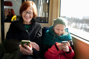 Sweden, Stockholm, Girl (10-11) with grandmother sitting in tram and using smart phonesの写真素材 [FYI02200733]