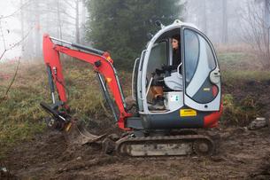 Sweden, Uppland, Nacka, Woman driving bulldozer in forestの写真素材 [FYI02200747]