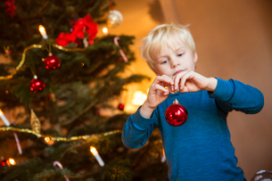 Sweden, Little blonde boy (4-5) with Christmas decoration toyの写真素材 [FYI02200796]