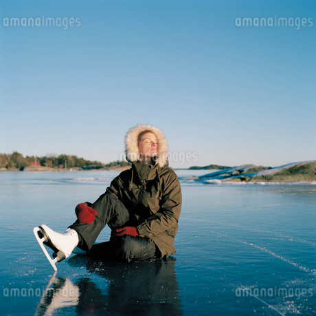 Sweden, Uppland, Varmdo, Bjorno, Mid adult woman sitting on frozen lakeの写真素材 [FYI02200806]