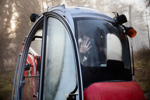 Sweden, Uppland, Nacka, Woman talking on phone in bulldozerの写真素材 [FYI02200819]