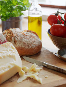 Sweden, Parmesan cheese and bread on cutting boardの写真素材 [FYI02200833]