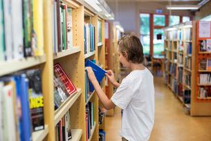 Sweden, Boy (12-13) choosing book in libraryの写真素材 [FYI02200849]
