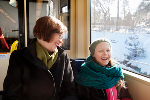 Sweden, Stockholm, Girl (10-11) sitting with grandmother in tram and laughingの写真素材 [FYI02200981]