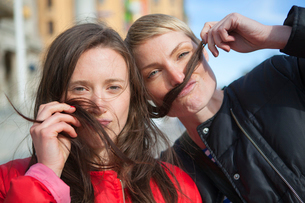 Sweden, Stockholm, Ostermalm, Two women playing with hairの写真素材 [FYI02201001]