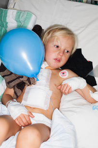 Sweden, Young boy (4-5) lying in hospital bedの写真素材 [FYI02201002]