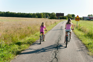 Sweden, Vastra Gotaland, Kallandso, Two girls (6-7, 12-13) cyclingの写真素材 [FYI02201016]