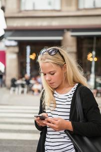 Sweden, Skane, Malmo, Teenage girl (14-15) using smart phone on streetの写真素材 [FYI02201026]
