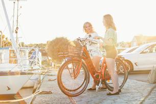 Sweden, Blekinge, Hallevik, Two teenage girls(14-15, 16-17) with bicycles standing at marina bay onの写真素材 [FYI02201027]