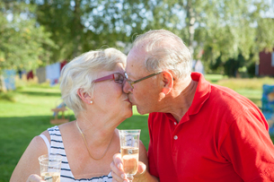 Sweden, Senior couple toasting with champagne flute and kissingの写真素材 [FYI02201043]