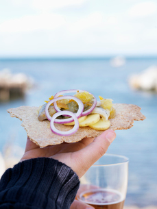 Sweden, Close- up of hand holding crispbread with pickled herring and onion ringsの写真素材 [FYI02201116]