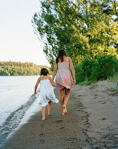 Sweden, Svealand, Malaren, Two barefoot girls (8-9, 16-17) walking by seaの写真素材 [FYI02201126]