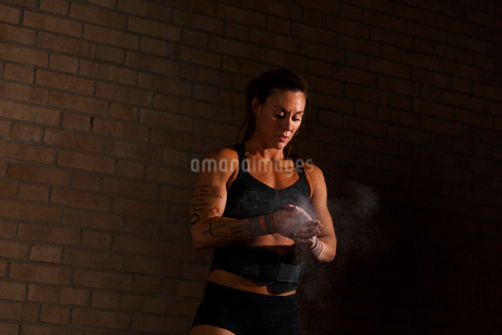Sweden, Young woman dusting hands with chalk in gymの写真素材 [FYI02201214]